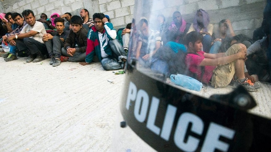 Migrants are guarded by a Greek policeman as they wait to be registered at a camp set up for migrants from Afghanistan near Moria on the island of Lesbos, Greece, Tuesday, Oct. 6, 2015. (Zoltan Balogh/MTI via AP)