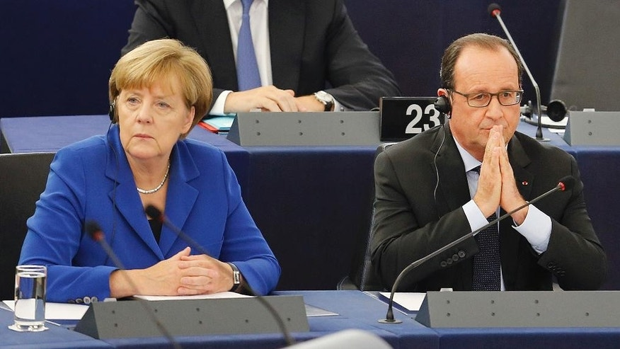 German Chancellor Angela Merkel, left, is seated next to French President Francois Hollande before addressing the members of the European Parliament in Strasbourg, eastern France, Wednesday, Oct. 7, 2015. Angela Merkel and Francois Hollande are making a historic appeal to the European Parliament on Wednesday. It's the first such joint appearance since 1989, when West German Chancellor Helmut Kohl and French President Francois Mitterrand spoke in Strasbourg days after the fall of the Berlin Wall. (AP Photo/Michael Probst)