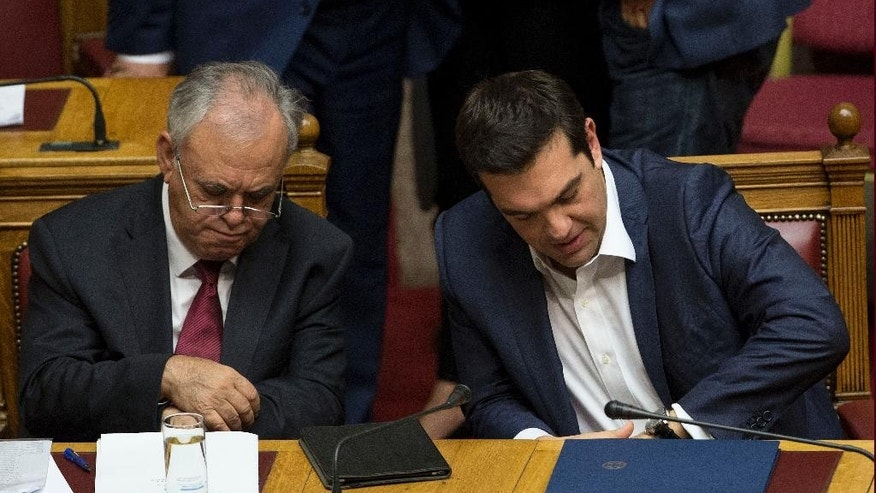 Greek Prime Minister Alexis Tsipras, right, and Greece's Deputy Prime Minster Yannis Dragasakis look at their watches during a parliamentary session before the confidence vote, in Athens, on Wednesday, Oct. 7, 2015. (AP Photo/Petros Giannakouris)