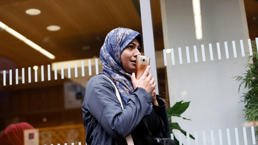 In this Thursday Sept.24, 2015 photo, Syrian refugee Amena Abomosa, 43, talks on a phone, prior to boarding a train to Vannes, western France, in the Montparnasse railway station, in Paris, France, Thursday, Sept. 24, 2015. Her slain husband, bombed-out Damascus home and refugee life are behind her. The recipient of a coveted asylum-seeker visa, Syrian teacher Amena Abomosa is settling into a new life in France with her family. But now what? They are among the few amid a sea of desperate Syrians to arrive in Europe with prior approval to seek haven. British Prime Minister David Cameron and other European leaders would prefer for all refugees to come this way – applying at European embassies abroad, undergoing careful screening and entering the EU legally. Everyone else, they argue, should stay away, instead of risking perilous journeys. (AP Photo/Thibault Camus)