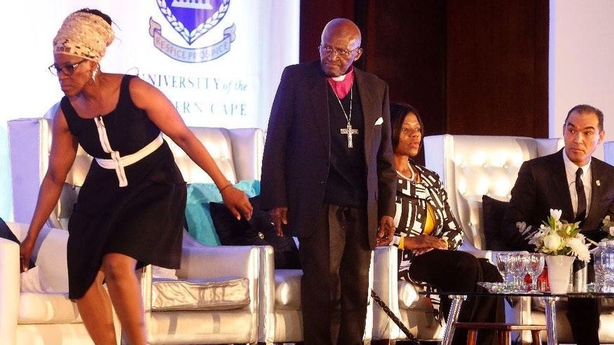 South Africa's Nobel Peace Prize winner Desmond Tutu, second left, next to his daughter Reverend Mpho Tutu, left, during  the fifth annual Desmond Tutu Peace Lecture at the University of the Western Cape in Cape Town, South Africa, Wednesday, Oct. 7, 2015. South Africa's Nobel Peace Prize winner Desmond Tutu marked his 84th birthday on Wednesday with one of his first public appearances since being hospitalized for a persistent infection.  (AP Photo/Schalk van Zuydam)