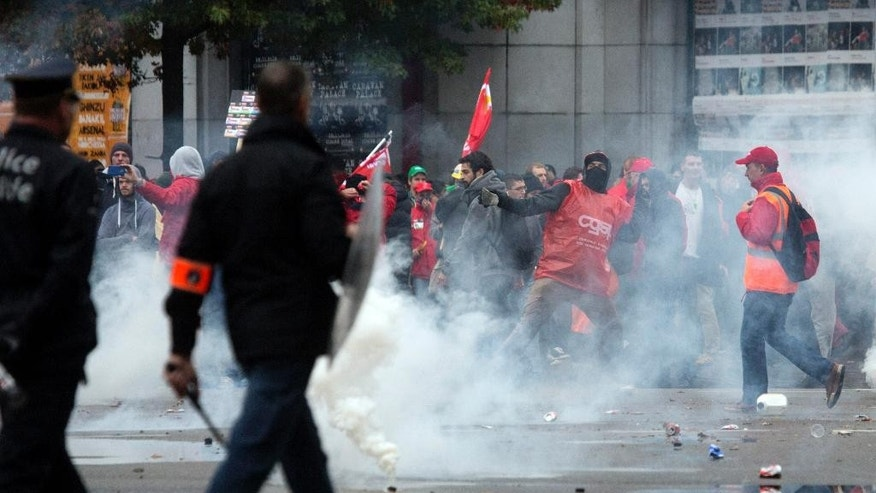 Demonstrators throw rocks at police during a trade union demonstration in Brussels on Wednesday, Oct. 7, 2015. Tens of thousands demonstrated against austerity measures the government has been pushing though its first year in office. (AP Photo/Virginia Mayo)