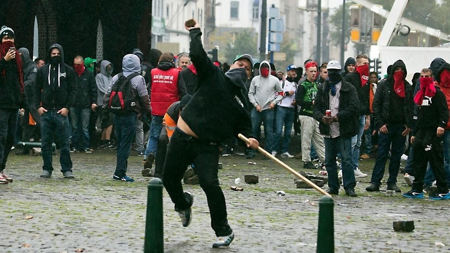 A demonstrator throws a rock toward a police line during a trade union demonstration in Brussels on Wednesday, Oct. 7, 2015. Tens of thousands demonstrated against austerity measures the government has pushing though during its first year in office. (AP Photo/Virginia Mayo)