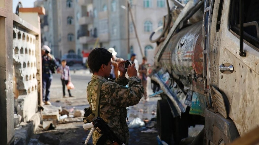 A Shiite fighter, known as a Houthi, uses his mobile to take pictures of a truck damaged at the site of a Tuesday night suicide bomb attack next to a mosque in Sanaa, Yemen, Wednesday, Oct. 7, 2015. The attack killed seven people and wounded three.  Islamic State militants claimed responsibility for the blast online.  (AP Photo/Hani Mohammed)
