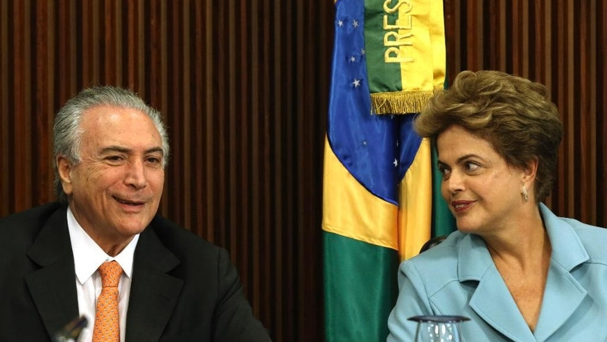 Brazil's President Dilma Rousseff looks over at Vice President Michel Temer, during a Cabinet meeting at the Planalto Presidential Palace in Brasilia, Brazil, Thursday, Oct. 8, 2015. Analysts say the Brazilian president's leadership capacity has been dealt a serious blow by a federal audit court ruling that her government violated accounting practices last year and broke the country's finance law by illegally using money from state banks to fill budget holes. They say the ruling could add fuel to efforts by Rousseff's opponents to begin impeachment proceedings against her in Congress. (AP Photo/Eraldo Peres)