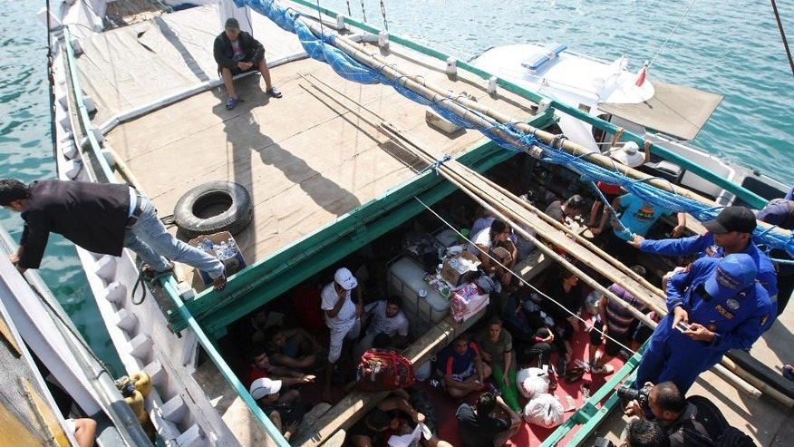 FILE - In this May 12, 2013 file photo, Iranian asylum seekers who were caught in Indonesian waters while sailing to Australia, sit on a boat, at Benoa port in Bali, Indonesia. Australia is in talks to send refugees who try to reach its shores illegally to the Philippines, the immigration minister said in Canberra Australia, Friday, Oct. 9, 2015. Australia refuses to accept any refugees who attempt to reach its shores by boat, and pays Nauru and Papua New Guinea, which has a detention center on Manus Island, to hold them instead. (AP Photo/Firdia Lisnawati)