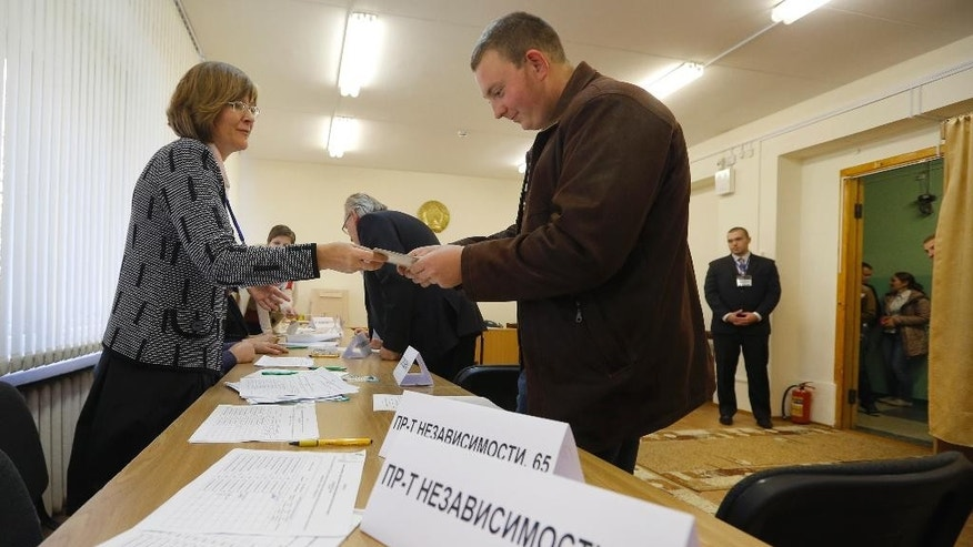 A Belarusian student receives his ballot paper at a polling station as early voting is held for Sunday's presidential election in Minsk, Belarus, Tuesday, Oct. 6, 2015. Presidential elections in Belarus are scheduled for October 11, 2015. (AP Photo/Sergei Grits)
