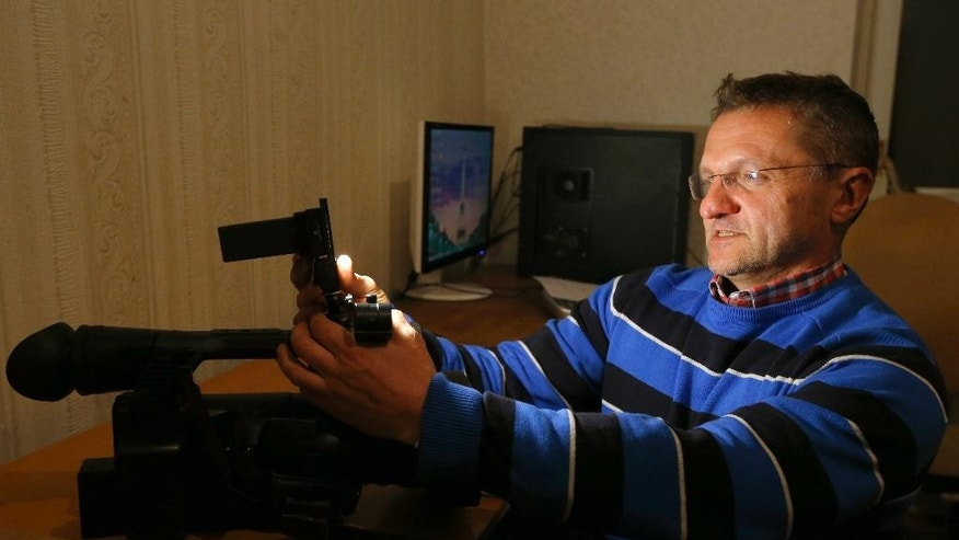 Belarusian journalist Alexander Silich adjusts light in his camera in an apartment where the independent Belsat television station has an office in Minsk, Belarus, Wednesday, Oct. 7, 2015. A secret apartment in an old Minsk building has become just the latest risky place for journalists from the independent Belsat television station to work. In the run-up to Sunday's presidential election, the government has gone after journalists like those at Belsat who seek to skirt state censorship by broadcasting from outside Belarus. (AP Photo/Sergei Grits)