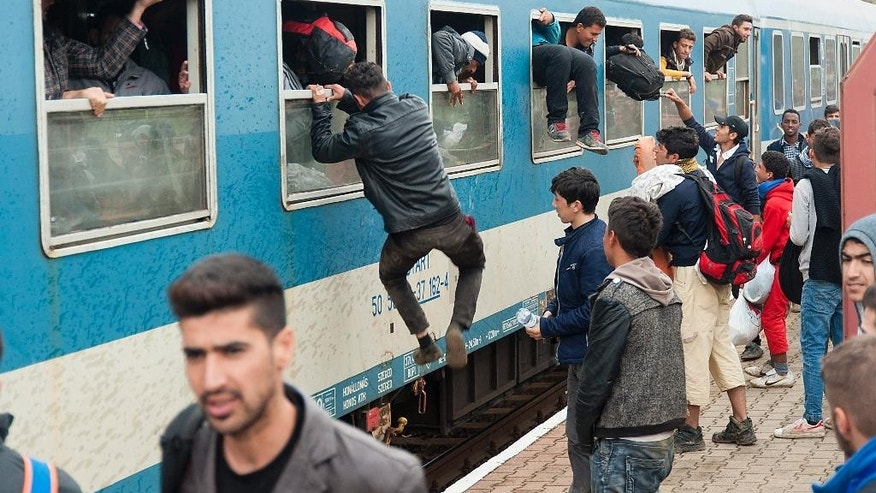 Migrants climb out of the windows of a train after they arrived at the railway station in Hegyeshalom, at the Austrian border, 169 kms west of Budapest, Hungary, Wednesday, Oct. 7, 2015. The migrants arrived here from the Croatian border to continue their journey to Austria. (Csaba Krizsan/MTI via AP)