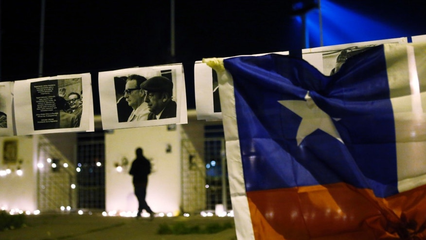 A Chilean national flag and pictures of former president Salvador Allende.
