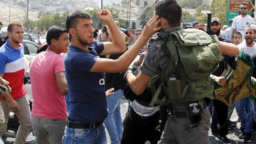 Oct. 2, 2015: An Israeli border policeman exchanges blows with a Palestinian man during a confrontation after Friday prayers outside the Old City in Jerusalem.