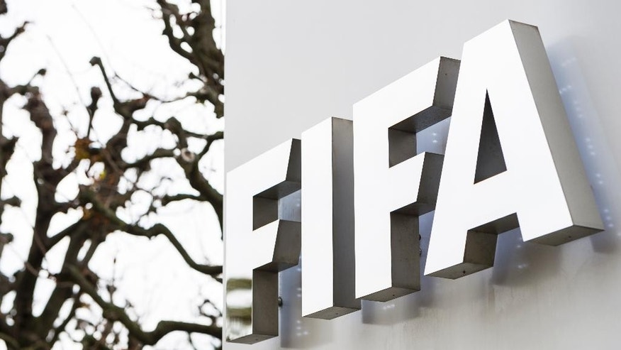 Trees are reflected in the FIFA logo at the FIFA headquarter in Zurich, Switzerland, Thursday, Oct. 8, 2015. FIFA provisionally banned President Sepp Blatter and UEFA President Michel Platini for 90 days. (Dominic Steinmann/Keystone via AP)