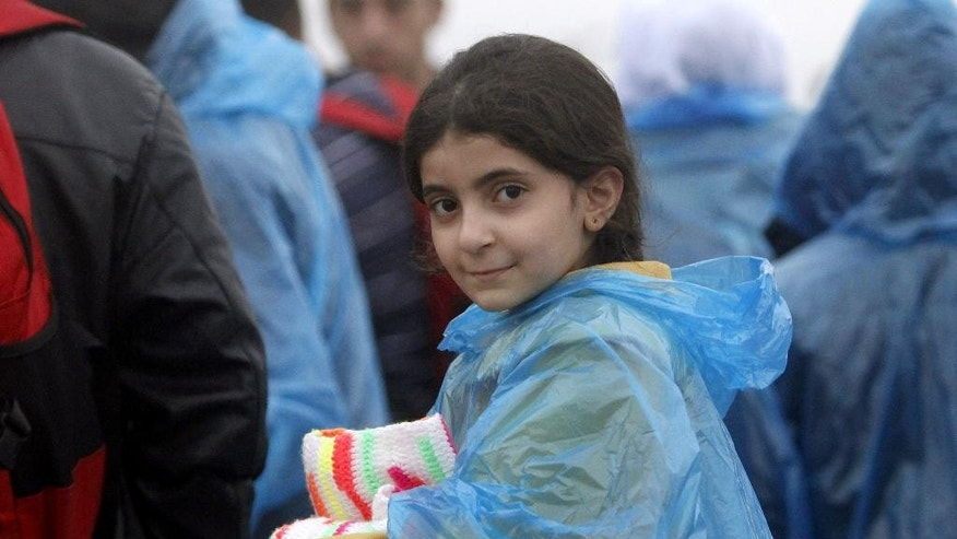 A girl in a raincoat arrives at the transit camp for refugees near the southern Macedonian town of Gevgelija, after crossing the border from Greece, on Thursday, Oct. 8, 2015. Several thousand migrants and refugees enter daily from Greece into Macedonia on their way through the Balkans towards the more prosperous European Union countries. More than 500,000 people have arrived this year in EU seeking sanctuary or jobs, sparking the EU's biggest refugee emergency in decades. (AP Photo/Boris Grdanoski)