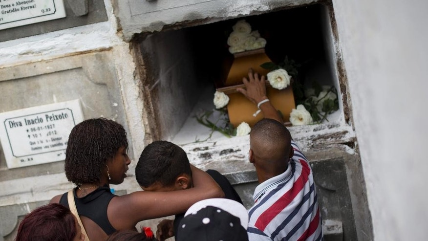 FILE - In this Sept. 30, 2015 file photo, relatives and friends of Eduardo Felipe Santos Victor, a teenager who was shot dead in the Morro da Providencia slum, mourn during his funeral in Rio de Janeiro, Brazil. Five Brazilian police officers were taken into custody for allegedly altering a crime scene by placing a gun in the hand of the seventeen-year-old, after they allegedly killed him during a shootout in a Rio de Janeiro. As he lay dying in a pool of blood, a slum resident shot video of one of the officers firing a handgun into the air and then putting the gun in Victor's hand. (AP Photo/Silvia Izquierdo, File)