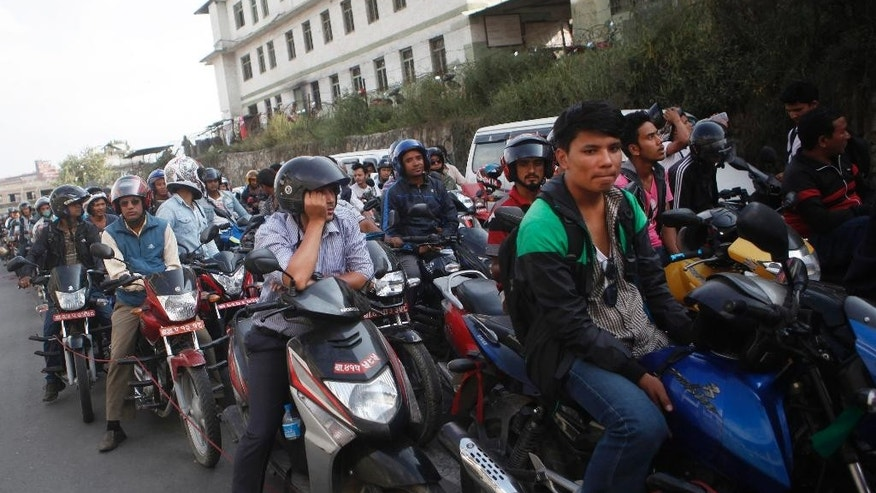 FILE - In this Sept. 28, 2015, file photo, Nepalese motorists wait for their turn to fill fuel in their motorbikes at a fuel pump run by the Nepalese army in Kathmandu, Nepal. Struggling with a fuel shortage after Indian shipments went on hold, Nepal is asking suppliers to bring gasoline and kerosene by airplane before the Himalayan country begins celebrating its biggest festival of the year, and for the first time is looking to import fuel in from China. (AP Photo/Niranjan Shrestha, File)