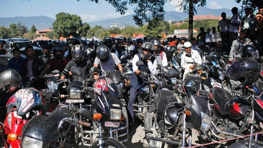 Nepalese people wait for their turn to fill fuel In their motorbikes at gas station run by Nepalese army in Kathmandu, Nepal, Thursday, Oct. 8, 2015. Struggling with a fuel shortage after Indian shipments went on hold, Nepal is asking suppliers to bring gasoline and kerosene by airplane before the Himalayan country begins celebrating its biggest festival of the year, and for the first time is looking to import fuel from China. (AP Photo/Niranjan Shrestha)