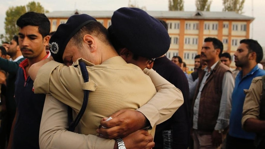 FILE - In this Wednesday, Oct. 7, 2015 file photo, Indian police officers embrace each other as they cry during the wreath laying ceremony of their colleague sub-inspector Mohammed Altaf in Srinagar, Indian. Suspected rebels gunned down the top police officer known for his successful counterinsurgency operations in Indian-controlled Kashmir, police said Thursday. (AP Photo/Mukhtar Khan, File)