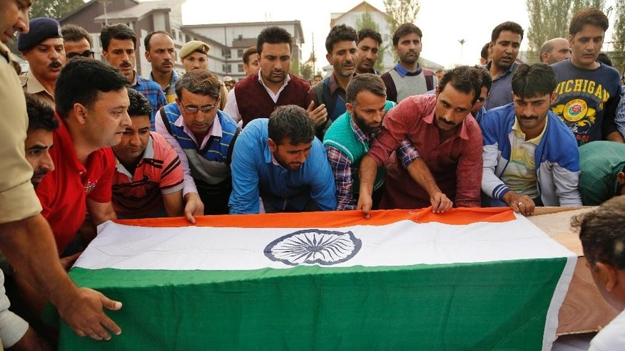 FILE - In this Wednesday, Oct. 7, 2015 file photo, unidentified relatives of sub-inspector Mohammed Altaf carry his coffin during a wreath laying ceremony in Srinagar, Indian. Suspected rebels gunned down the top police officer known for his successful counterinsurgency operations in Indian-controlled Kashmir, police said Thursday. (AP Photo/Mukhtar Khan, File)