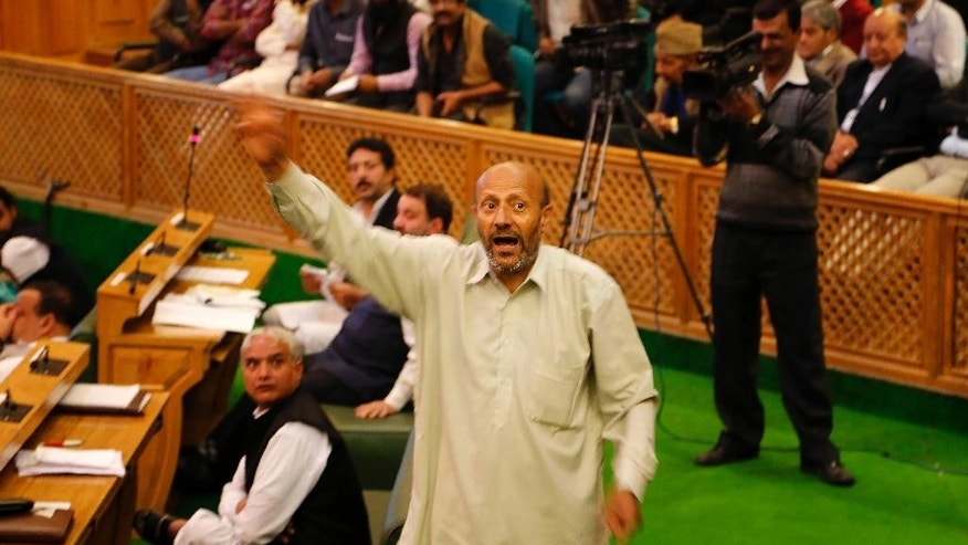 Engineer Rashid Ahmed, a Jammu and Kashmir state lawmaker, shouts as he protests inside the state legislature house in Srinagar, Indian controlled Kashmir, Thursday, Oct. 8, 2015. Lawmakers from India's ruling Hindu nationalist party Bharatiya Janata Party (BJP) in Kashmir kicked and punched Ahmed, independent member of the state assembly on Thursday for hosting a party where he served beef. Hindus consider cows to be sacred, and slaughtering the animals is banned in most Indian states. (AP Photo/Mukhtar Khan)