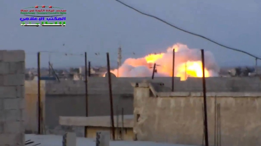 This image taken from video provided by the Syrian activist-based media group Syrian Revolutionary Command Council in Hama, which has-been verified and is consistent with other AP reporting, shows smoke rising after a Russian airstrike hit buildings in the town of Latamna in the area of Hama in Eastern Syria, Wednesday, Oct. 7, 2015. (Syrian Revolutionary Command Council in Hama via AP Video)