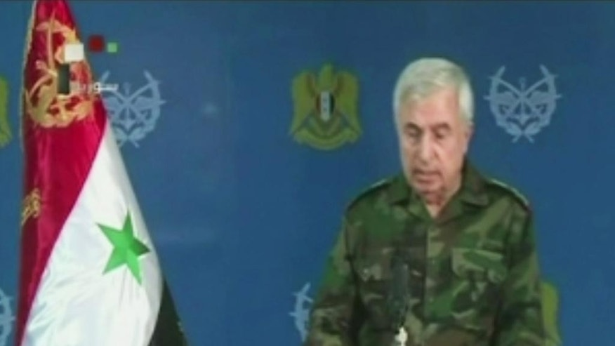 "In this frame grab from video provided taken from Syrian TV via Al Manar, Gen. Ali Ayoub, Syria's chief of staff, speaks, Thursday, Oct. 8, 2015, in Damascus, Syria. Ayoub said in a rare televised statement that the Russian strikes on Syria have facilitated an expanded military operation to eliminate ""terrorists,"" a term the Syrian government uses to refer to all armed opposition to President Bashar Assad. (Al Manar via AP)"