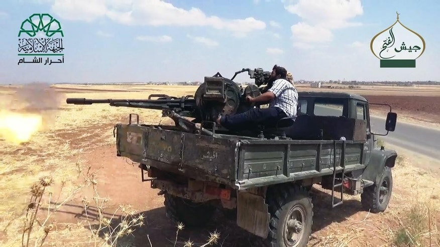In this image posted on the Twitter page of Ahrar al-Sham on Aug. 8, 2015, a fighter from the al-Qaida-linked Ahrar al-Sham fires his weapon against pro-government fighters in the northwestern village of Foua in Idlib province, Syria. In an effort to improve its image in the West, the group's self-styled foreign affairs director has written opinion pieces in the Washington Post and Britain's Daily Telegraph to present his group as a moderate alternative and potential partner for Western governments. (Ahrar al-Sham Twitter page via AP)