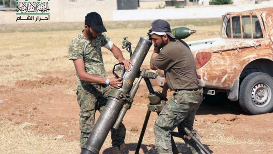 In this image posted on the Twitter page of Ahrar al-Sham on Aug. 13, 2015, fighters from Ahrar al-Sham prepare a mortar to shell Islamic State group positions near the northern town of Azaz in Aleppo province, Syria. In an effort to improve its image in the West, the group's self-styled foreign affairs director has written opinion pieces in the Washington Post and Britain's Daily Telegraph to present his group as a moderate alternative and potential partner for Western governments. (Ahrar al-Sham Twitter page via AP)