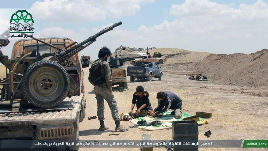 "In this image posted on the Twitter page of Ahrar al-Sham on Aug. 13, 2015, fighters from Ahrar al-Sham prepare weapons ahead of an attack on Islamic State group positions in Aleppo province, Syria. The group has vowed to defeat what it calls Russian ""occupation"" of Syria after Moscow began launching airstrikes on insurgents last week. (Ahrar al-Sham Twitter page via AP)"
