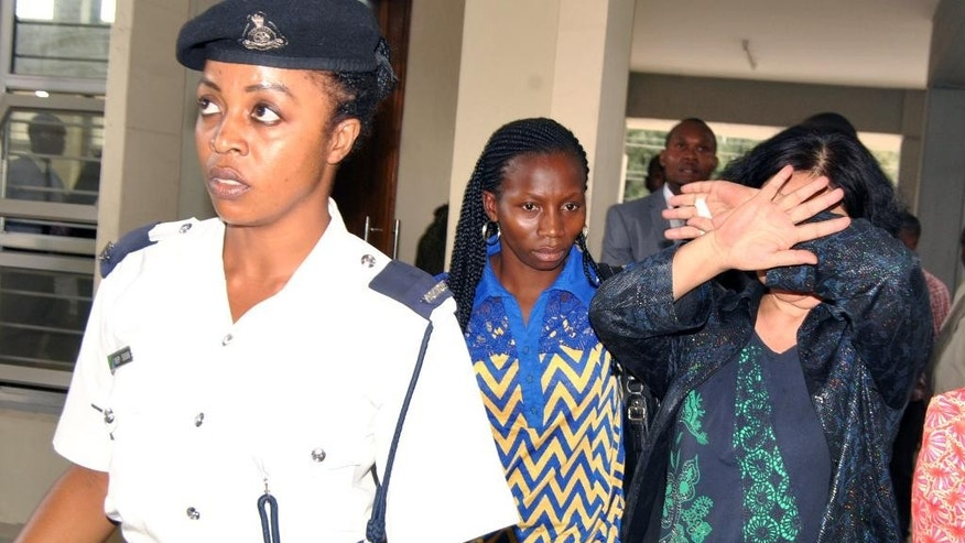 In this photo taken on Wednesday Oct. 7, 2015, Chinese national Young Feng Glan , right, covers her face as she is escorted by police from Kisutu Resident's Magistrate Court in Dar es Salaam, Tanzania. A Chinese woman has been charged in a Tanzanian court with smuggling nearly 1.9 tons of ivory as wildlife activists applauded the move by Tanzanian authorities to crack down on the illegal ivory trade, which has devastated the elephant population in just a few years. Businesswoman Yang Feng Clan, 66, was charged Wednesday in Dar es Salaam alongside two Tanzanian men. The three suspects allegedly committed the crime between Jan. 1, 2000 and May 22, 2014. Their case was adjourned to Monday. (AP photo)