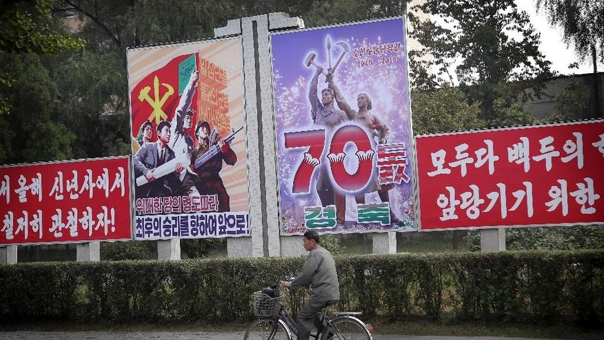 A man cycles past a signboard marking the upcoming 70th anniversary of the founding of North Korea's Workers' Party, Thursday, Oct. 8, 2015, in Pyongyang, North Korea. The country is in high gear with preparations for the anniversary on Oct. 10. 2015. (AP Photo/Wong Maye-E)