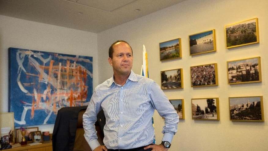 In this Thursday, Oct. 8, 2015 photo, Jerusalem Mayor Nir Barkat, poses for a photograph during an interview with The Associated Press in his Jerusalem office. Barkat, caught on video this week with a gun slung over his shoulder while visiting a Palestinian neighborhood, is making no apologies for the display of force. In the interview Barkat urged other licensed gun owners to follow his lead. (AP Photo/Tsafrir Abayov)