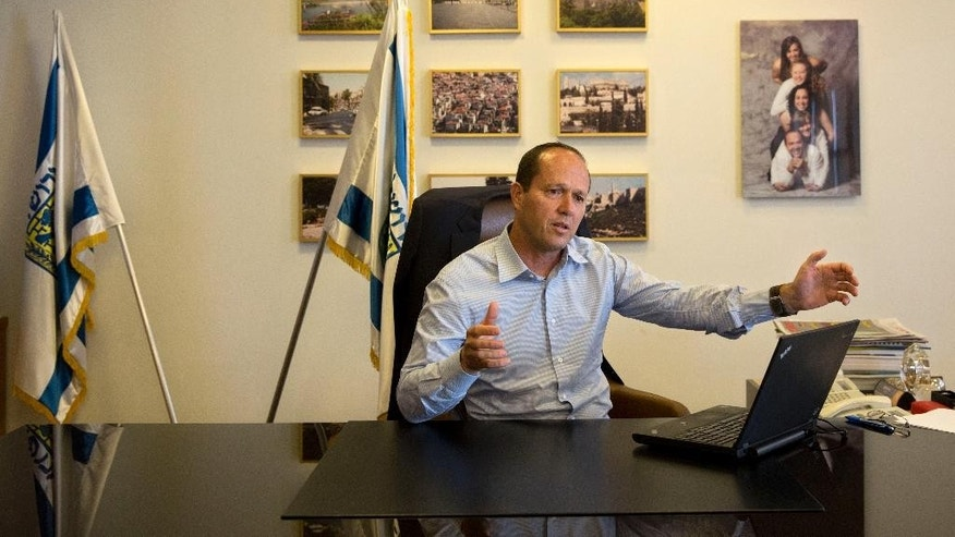 In this Thursday, Oct. 8, 2015 photo, Jerusalem Mayor Nir Barkat, speaks during an interview with The Associated Press in his Jerusalem office. Barkat, caught on video this week with a gun slung over his shoulder while visiting a Palestinian neighborhood, is making no apologies for the display of force. In the interview Barkat urged other licensed gun owners to follow his lead. (AP Photo/Tsafrir Abayov)