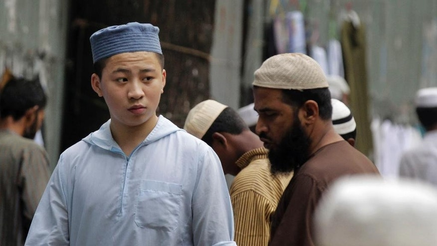 In this Oct. 6, 2015 photo, a foreigner Muslim devotee walks on a street outside a mosque early morning in Dhaka, Bangladesh. The recent killings of two foreigners in the country - an Italian and a Japanese - has spooked tourists and expatriates in the impoverished South Asian nation, raising alarms about whether Islamic radicals are gaining a foothold and whether foreigners are safe in the moderate, secular nation. (AP Photo/A.M. Ahad)