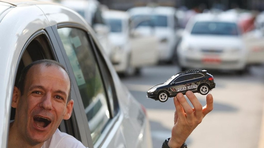 "A taxi driver holds a toy car during a protest against the ride-booking company Uber, next to City Hall in downtown Sao Paulo, Brazil, Thursday, Oct. 8, 2015. The text on the toy car reads in Portuguese ""Uber out."" Sao Paulo will introduce new regulations to govern Uber instead of banning it. (AP Photo/Andre Penner)"
