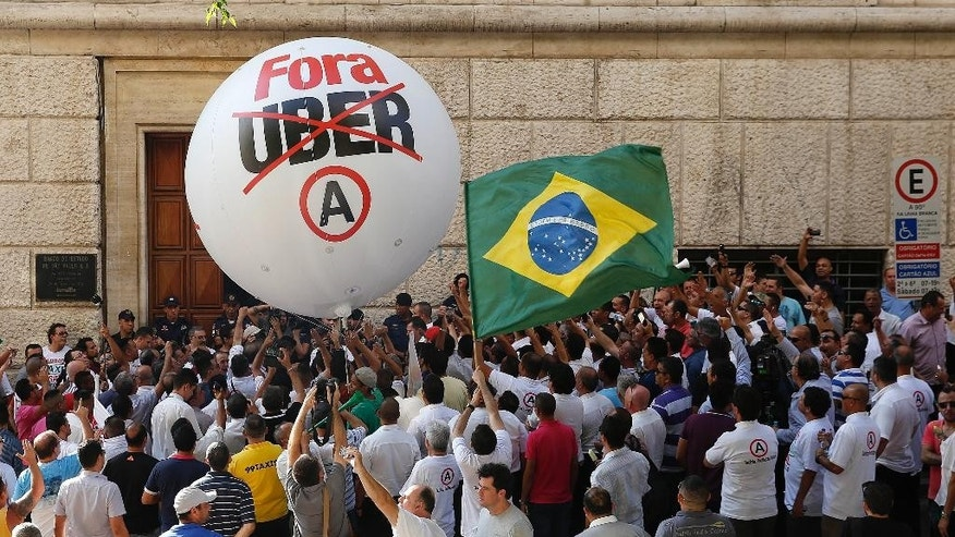 Taxi drivers protest against the ride-booking company Uber outside the City Hall in downtown Sao Paulo, Brazil, Thursday, Oct. 8, 2015. Sao Paulo will introduce new regulations to govern Uber instead of banning it. (AP Photo/Andre Penner)