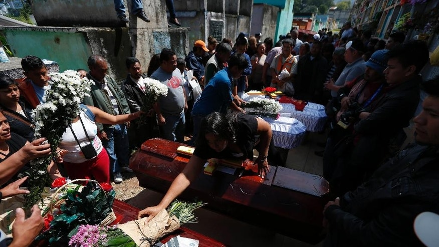A woman places flowers over a coffin during the burial of five mudslide victims inside the Santa Catarina Pinula cemetery on the outskirts of Guatemala City, Tuesday, Oct. 6, 2015. Prosecutors in Guatemala said Tuesday they have opened an investigation into who allowed homes to be built in an unsafe area where a massive mudslide killed more than 100 people. (AP Photo/Moises Castillo)
