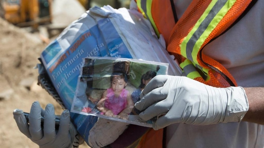 Samuel Morales, who survived a mudslide but is still searching for his missing family, holds a photo of his 4-year-old daughter Jaquelin in Cambray, a neighborhood in the suburb of Santa Catarina Pinula, on the outskirts of Guatemala City, Friday, Oct. 9, 2015. The death toll of the massive landslide has risen to more than 250 as the search for victims entered its second week. (AP Photo/Moises Castillo)