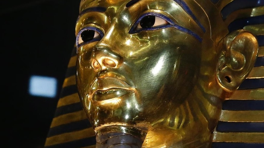 FILE - In this Saturday, Jan. 24, 2015, file photo, the gold mask of King Tutankhamun is seen in its glass case during a press tour, in the Egyptian Museum near Tahrir Square, Cairo, Egypt. The restoration of King Tutankhamun's world-famous golden mask will begin Saturday, over a year after the beard was accidentally broken off and hastily glued back with epoxy, Egypt's state-run news agency said Friday. (AP Photo/Hassan Ammar, File)