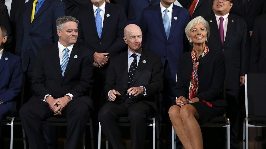 International Monetary Find (IMF) Managing Director Christine, right, sits next to Glenn Robert Stevens, Governor of the Reserve Bank of Australia, center, and  Mathias Cormann, Minister for Finance of Australia, before a group picture with Finance Ministers and Central Bank Governors from the G20 in Lima, Peru, Thursday, Oct. 8, 2015. The world's finance ministers and central bankers are in Lima for the joint annual meetings of the World Bank and IMF that run through Sunday. (AP Photo/Geraldo Caso Bizama)