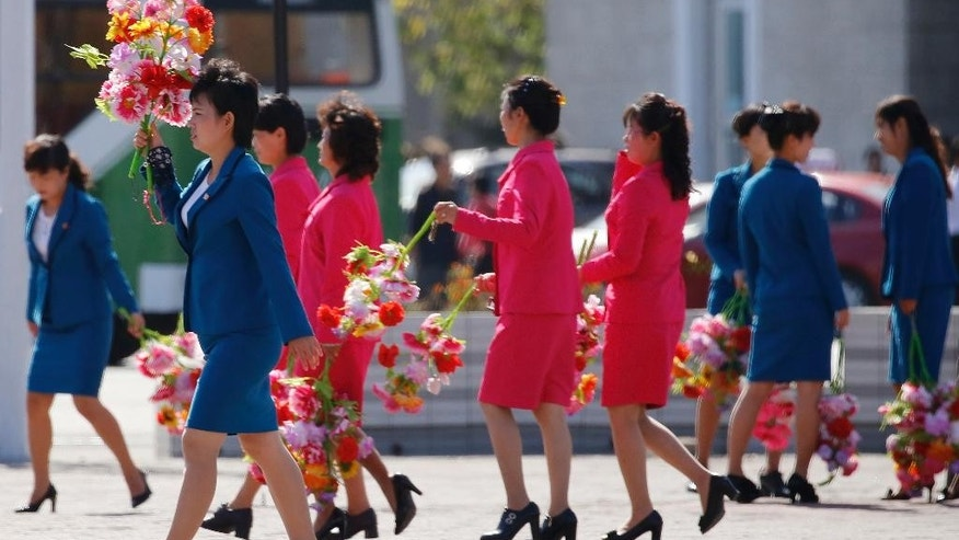Women walk on a plaza with decorative flowers Friday, Oct. 9, 2015, ahead of Saturday's anniversary celebrations in Pyongyang, North Korea. The country is preparing for the 70th anniversary of the founding of the North Korea Workers' Party on Oct. 10, 2015. (AP Photo/Charles Dharapak)