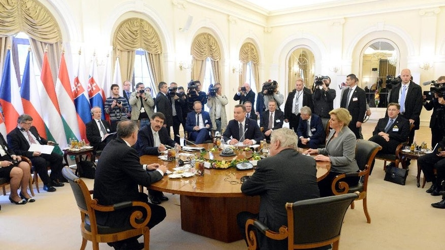 Presidents Andrej Kiska of Slovakia, Janos Ader of Hungary, Andrzej Duda of Poland, Kolinda Grabar-Kitarovic of Croatia and Milos Zeman of the Czech Republic, clockwise, sit at the conference table during the meeting of heads of state of the Visegrad Group countries in Balatonfured, 125 km southwest of Budapest, Hungary, Friday, Oct. 9, 2015. (Tamas Kovacs/MTI via AP)