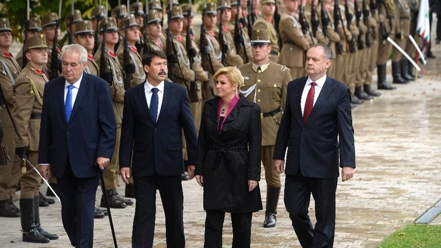 From left, Presidents Milos Zeman of the Czech Republic, Janos Ader of Hungary, Kolinda Grabar-Kitarovic of Croatia and Andrej Kiska of Slovakia inspect the honour guards during a meeting of heads of state of the Visegrad Group countries in front of Anna Grand Hotel in Balatonfured, 125 km southwest of Budapest, Hungary, Thursday, Oct. 8, 2015. (Tamas Kovacs/MTI via AP)