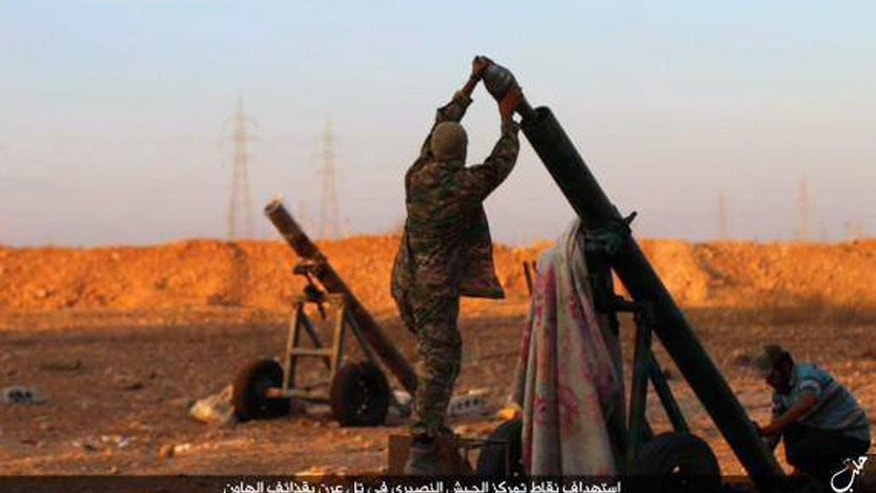 "In this image posted on Thursday, Oct. 8, 2015, by the Rased News Network, a Facebook page affiliated with Islamic State, shows Islamic State militants preparing to fire a mortar to shell towards Syrian government forces positions at Tal Arn in Aleppo province, Syria. Islamic State militants seized several villages from rival insurgents north of Aleppo city Friday, in a surprise attack that came despite intensive Russian airstrikes that Moscow insists are targeting the extremist group, activists said. Arabic reads, ""Targeting positions of the Alawite army in Tal Arn with mortar shells."" (Islamic State militant website via AP)"