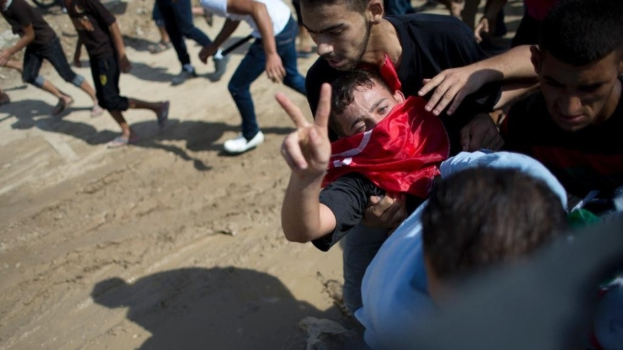 Palestinians carry a wounded man, who flashes a victory sign, as others run for a cover, during clashes with with Israeli soldiers on the Israeli border, Eastern Gaza City, Friday, Oct. 9, 2015. At least four attacks — three by Palestinians and one by an Israeli — as well as deadly clashes along the Gaza border threatened to escalate tensions throughout the country on Friday as Israel struggled to control spiraling violence. (AP Photo/ Khalil Hamra)