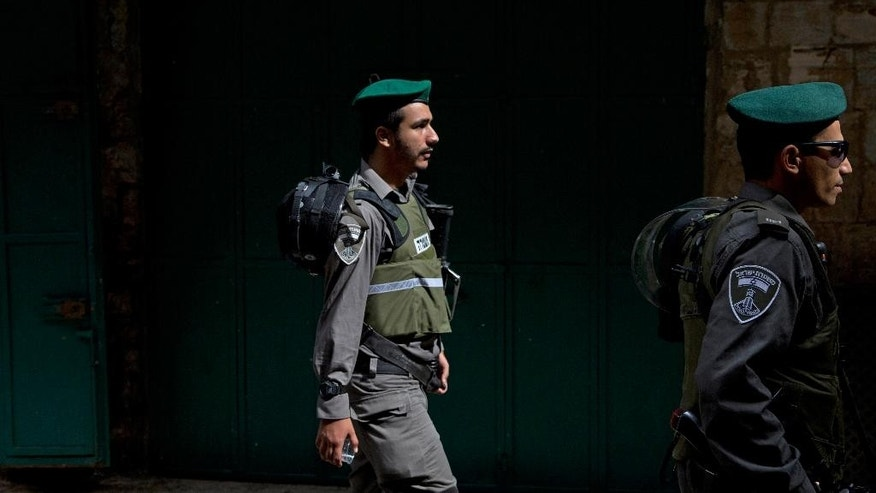 Israeli border police officers walk in the Old City of Jerusalem before Friday's Muslim prayers Friday, Oct. 9, 2015. A rash of individual attacks between Palestinians and Israelis threatened to spread throughout Israel Friday as a 14-year-old Israeli and a police officer were stabbed in separate incidents while an Israeli stabbed four Arabs in the southern city of Dimona. A Palestinian woman pulled out a knife and tried to stab a security guard at the bus station in Afula, in northern Israel Friday afternoon, police said. The guard opened fire and injured the Palestinian before she could hurt anybody, police said. (AP Photo/Ariel Schalit)