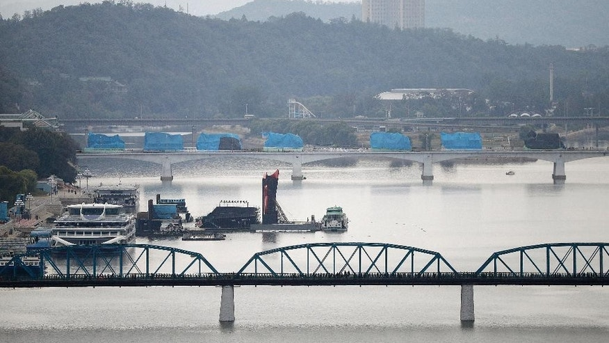 Military vehicles or possibly floats shrouded in blue plastic tarps to protect them against the weather are parked in a long row on a bridge leading to the parade route, Saturday, Oct. 10, 2015, in Pyongyang, North Korea. North Korea is holding what is expected to be one of its biggest celebrations ever Saturday for the 70th anniversary of its ruling party's creation, an attention-getting event that is the government's way of showing the world and its own people the Kim dynasty, now in its third generation, is firmly in control and its military a power to be reckoned with. (AP Photo/Wong Maye-E)