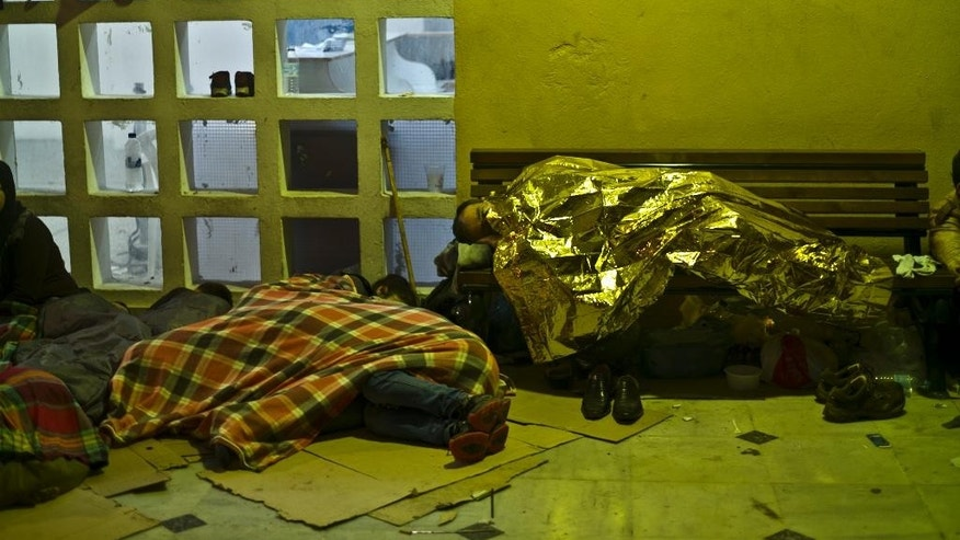 A refugee sleeping on a bench wraps himself with a thermal blanket to shelter from the morning cold at the port of Mitylene on the northeast Greek island of Lesbos, while waiting to get on board a ferry traveling to Athens, early Friday, Oct. 9, 2015. More than 500,000 people have arrived in the European Union this year, seeking sanctuary or jobs and sparking the EU's biggest refugee emergency in decades. (AP Photo/Muhammed Muheisen)