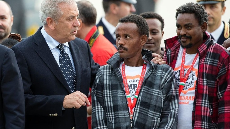 European Commissioner for Migration and Home Affairs Dimitris Avramopoulos, left, speaks to Eritrean refugees waiting to board an Italian Financial police aircraft which will take them to Sweden, at Rome's Ciampino airport, Friday, Oct. 9, 2015. The aircraft, carrying 19 Eritreans, will bring the first refugees to Sweden under the European Union's new resettlement program aimed at redistributing asylum-seekers from hard-hit receiving countries. (AP Photo/Andrew Medichini)