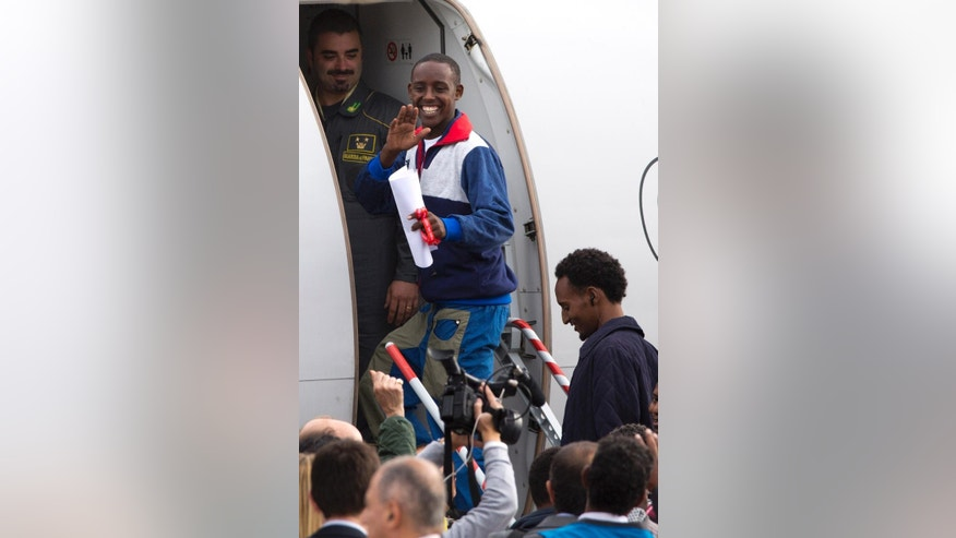 An Eritrean refugee waves as he boards an Italian Financial police aircraft which will take him and other 18 refugees to Sweden, at Rome's Ciampino airport, Friday, Oct. 9, 2015. The aircraft brings the first refugees to Sweden under the European Union's new resettlement program aimed at redistributing asylum-seekers from hard-hit receiving countries. (AP Photo/Andrew Medichini)