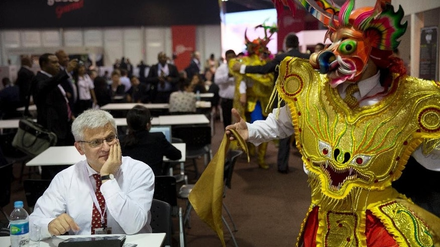 "A man attending the annual meetings by the World Bank Group and IMF watches a man perform a traditional dance from Puno, Peru called ""La Diablada"" inside the venue's dining area in Lima, Peru, Friday, Oct. 9, 2015. More than 60 percent of Peruvians workers are in the informal economy, according to U.N. figures, spending on health care and education are below regional averages and most government revenues come not from income tax but rather taxes on sales and consumption, putting the burden disproportionately on the poor in the region with the world's most unequal wealth distribution. (AP Photo/Rodrigo Abd)"